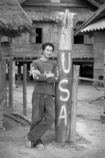 Sou Lin Phan poses next to a large dud bomb in the middle of his village. Over several years in the late 60s and early 70s, the US dropped 4 billion pounds of explosives on northern Laos in a futile effort to stop North Vietnamese soldiers from using the area as a base and transshipment line to South Vietnam.  As much as 30 percent of the bombs dropped did not explode and they can be seen around the countryside today. They also pose a continuing threat to life.